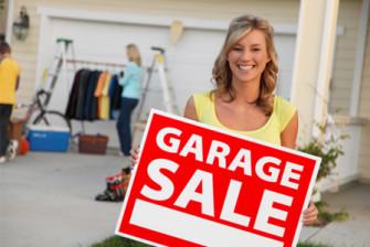 woman-holding-garage-sale-sign-horiz